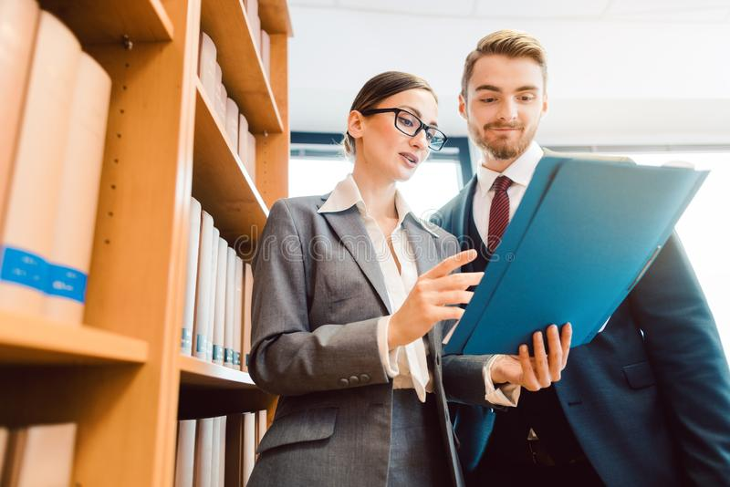 Lawyers in library of law firm discussing strategy in a case holding file. Two lawyers in library of law firm discussing strategy in a case holding file stock photos
