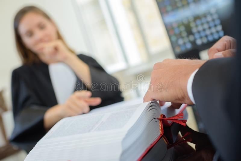 Lawyers in robes looking in legal book stock photos