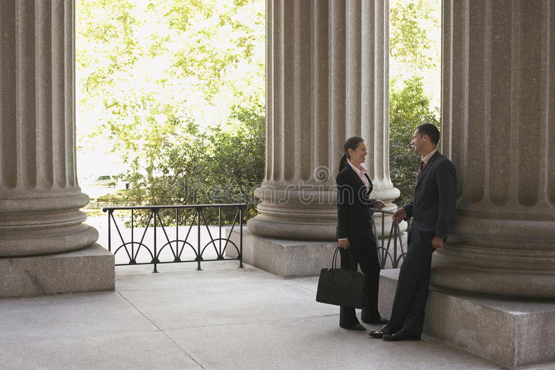 Lawyers Talking At Courthouse. Full length side view of two attorneys talking at courthouse royalty free stock photo