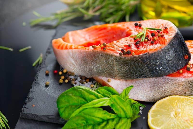 Lax Rå forellfiskbiff med örter och citronen på svart kritiserar bakgrund matlagning royaltyfri fotografi