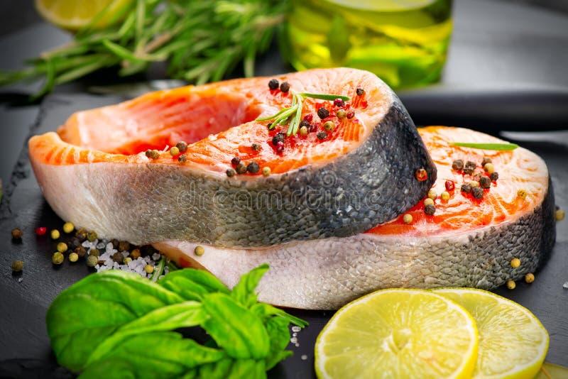 Lax Rå forellfiskbiff med örter och citronen på svart kritiserar bakgrund Matlagning skaldjur arkivfoto