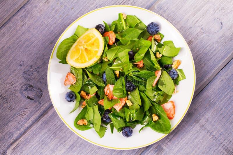 Lax, spenat, blåbär och valnötsallad på den vita plattan arkivfoton