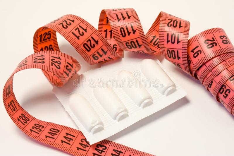Laxatives odbytniczy suppositories w pakunku i pomiarowej taśmie wokoło Używać laxatives medycyny dla ciężaru taktować obesit i s zdjęcie stock