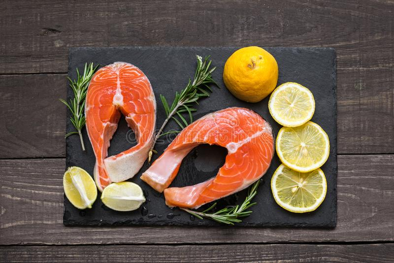 Laxbiff som är rik i omega 3 som är olje-, med rosmarin, och citronen på svart kritiserar brädet arkivbild