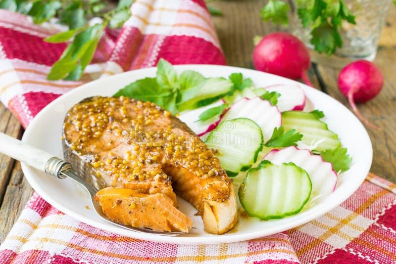 Laxbiff som bakas i honung och senapsgult marinad Lax på en vit platta med nya grönsaker spelrum med lampa royaltyfria foton
