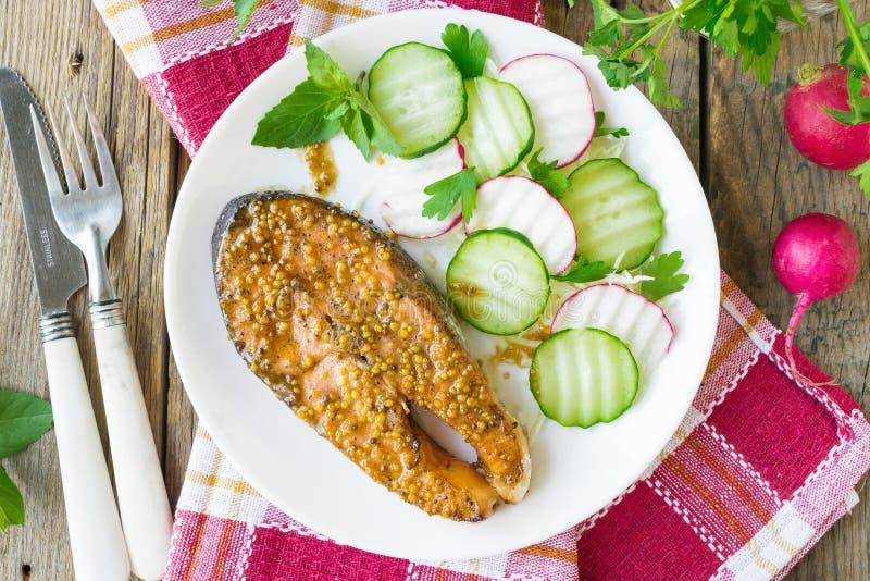 Laxbiff som bakas i honung och senapsgult marinad Lax på en vit platta med nya grönsaker spelrum med lampa royaltyfri foto