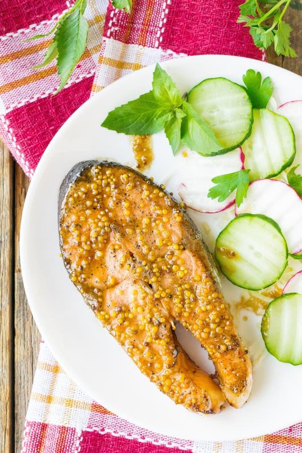 Laxbiff som bakas i honung och senapsgult marinad Lax på en vit platta med nya grönsaker spelrum med lampa arkivbild