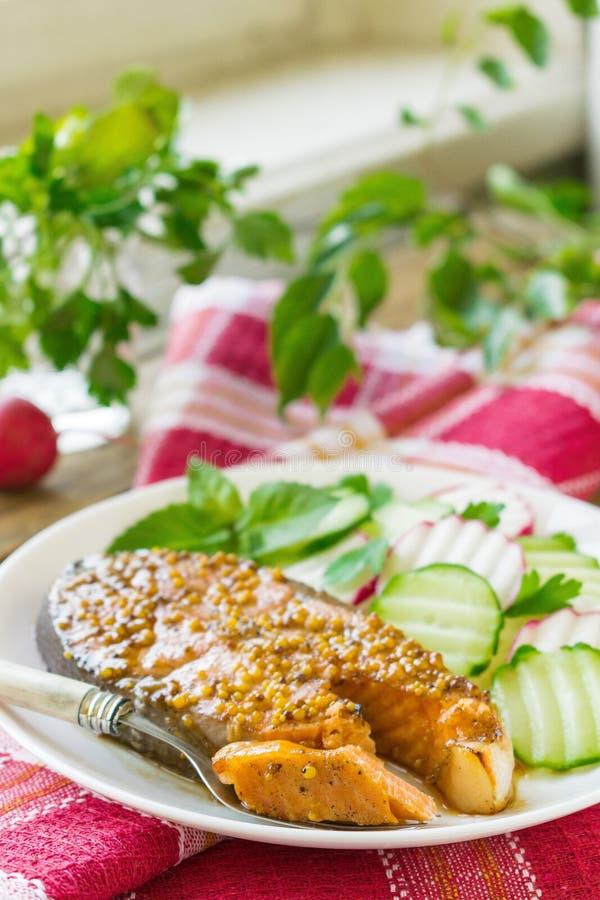 Laxbiff som bakas i honung och senapsgult marinad Lax på en vit platta med nya grönsaker spelrum med lampa fotografering för bildbyråer