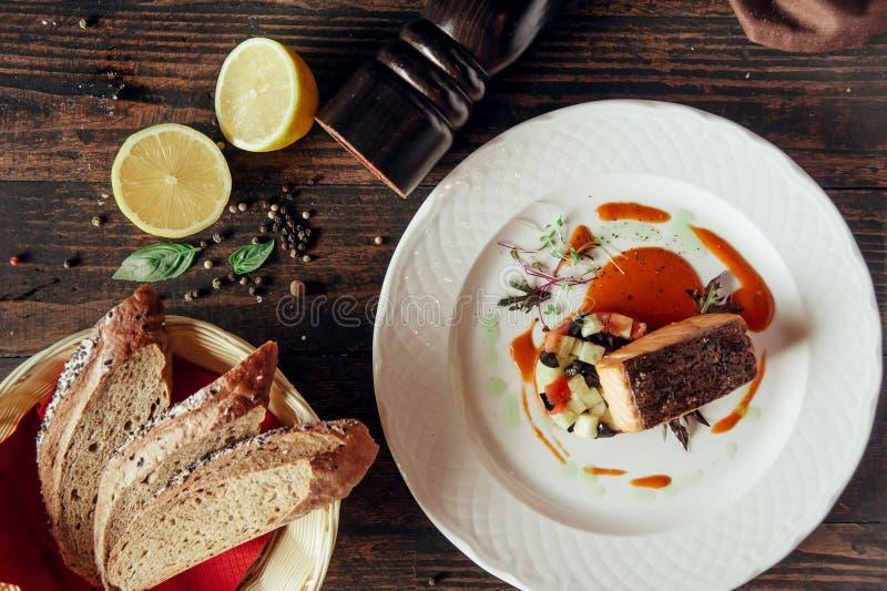 Laxfisken grillade biff som dekorerades med bröd och citronen på mörk träbakgrund fotografering för bildbyråer