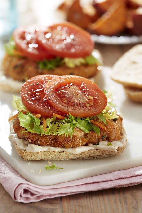 Laxhamburgare med grönsallat, den mayo dressingen och tomater arkivfoton