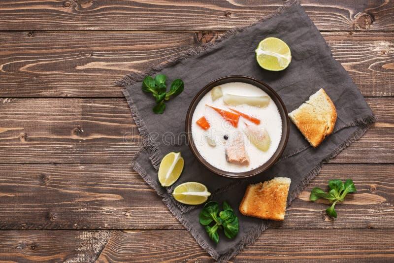 Laxsoppa med potatisar, morötter, kräm Skandinav norsk fisksoppa på en lantlig träbakgrund Sikt från arkivfoton