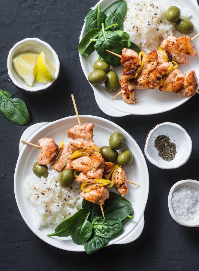 Laxsteknålar och ris - sund lunchtabell Grillad laxfisksteknål på en mörk bakgrund arkivfoton