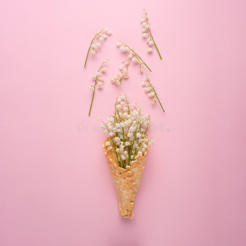 Lay cukierki rożka opłatki z lelują dolina biali migdałowi kwiaty nad pastelu światłem - różowy tło, odgórny widok przeciw jako t obraz stock
