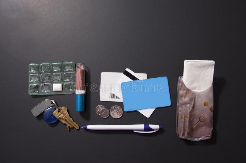 Lay flat purse contents. Contents of what might be in a person`s purse or bag royalty free stock photos