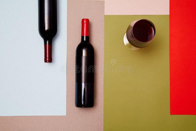 Lay-out van flessen en glas rode wijn op kleurrijke document achtergrond stock foto's
