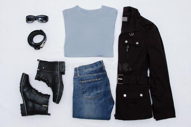 Lay-outkleren Zwart jasje, laarzen, riem, glazen, jeans en grijze T-shirt Mening van hierboven Witte achtergrond stock foto