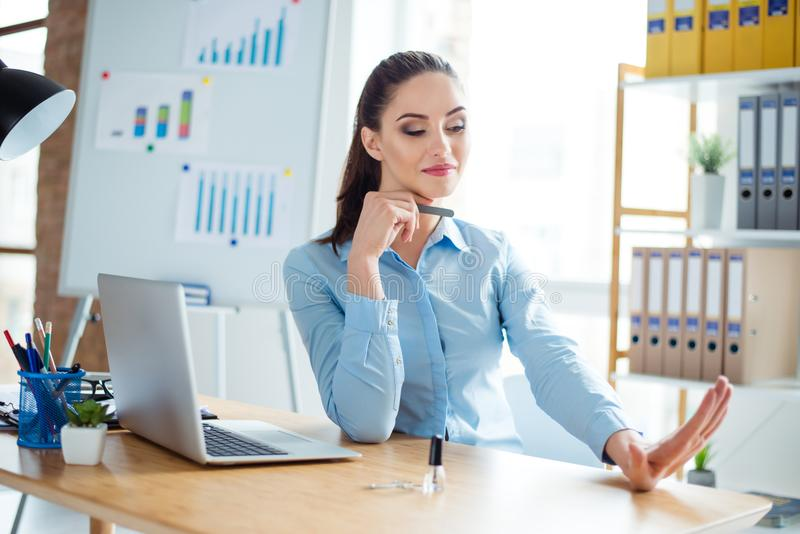 Layabout concept. Portrait of young cheerful cute woman in formal wear with pony tail, filing nails at her work station in office royalty free stock photo