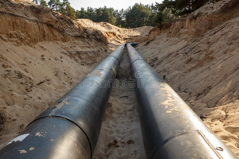 Layed pipeline construction. A uncovered pipeline construction site with sand around it royalty free stock photos