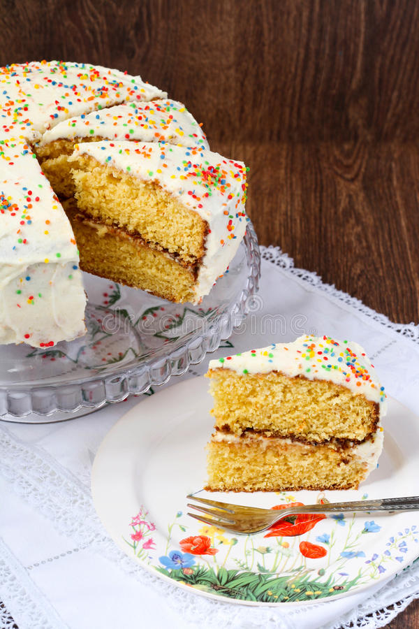 Layer cake. Slice of layer cake with white frosting decorated with hundreds and thousands royalty free stock photography