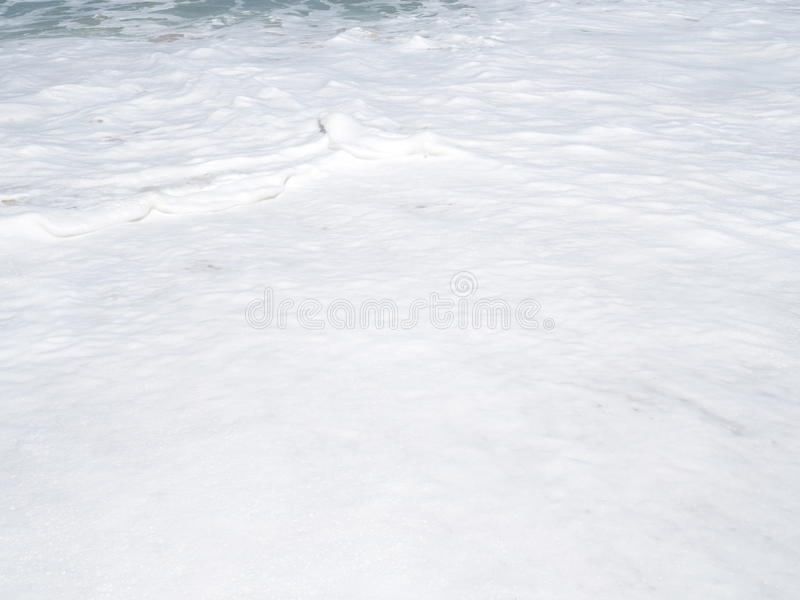 Layer of soft white sea wave foam lapping on sand beach. Layer of soft white sea wave foam lapping on sand beach royalty free stock image