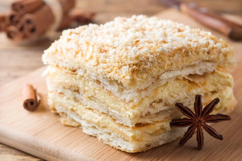 Layered cake with cream Napoleon millefeuille vanilla slice with cinnamon and anise on wooden background.  royalty free stock image