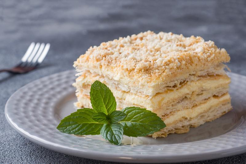 Layered cake with cream Napoleon millefeuille vanilla slice with mint on dark background.  royalty free stock images