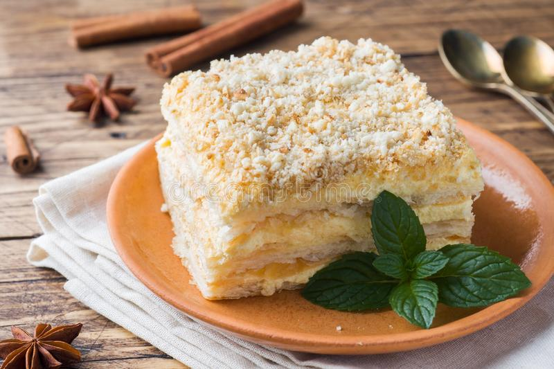 Layered cake with cream Napoleon millefeuille vanilla slice with mint on wooden background.  stock photos