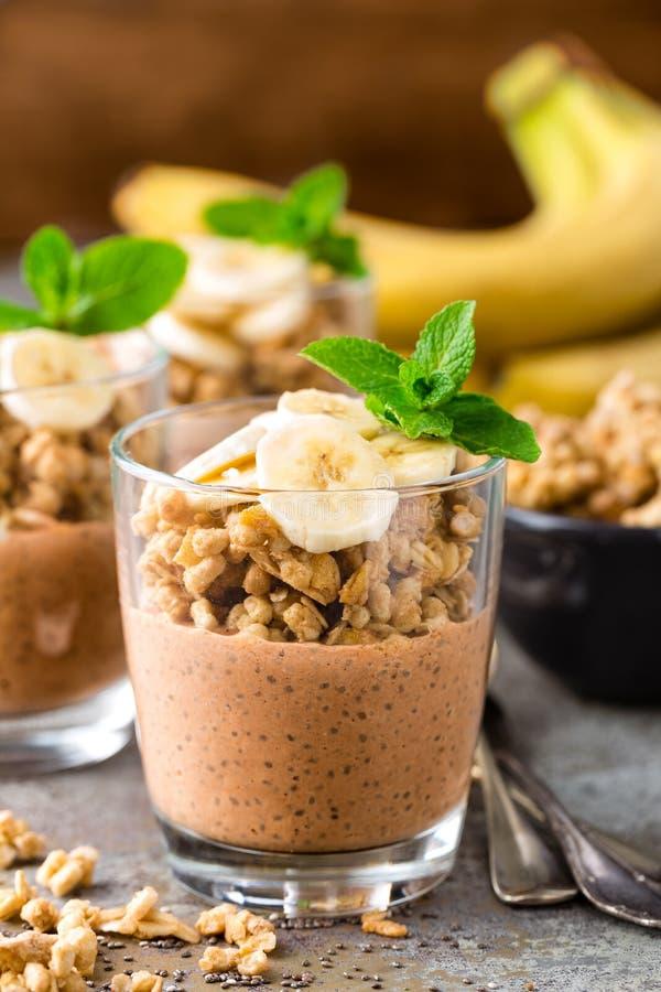 Layered chocolate chia pudding parfait with banana, granola and yogurt, dessert royalty free stock photography