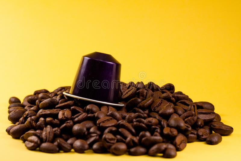 Layered coffee capsule, across a yellow background, with brown coffee beans under it. Coffee shop and food stock image