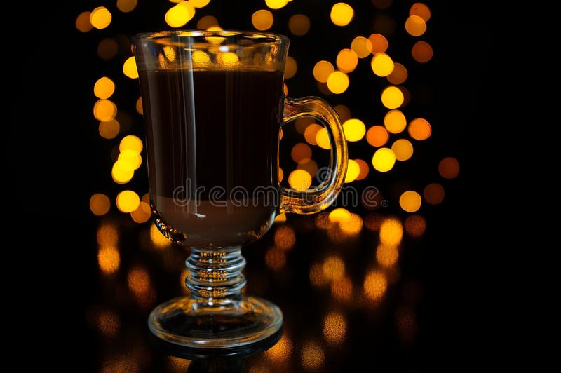 Layered Coffee Cocktail Against Dark Glowing Background. A layered coffee cocktail in glass against dark glowing background royalty free stock image