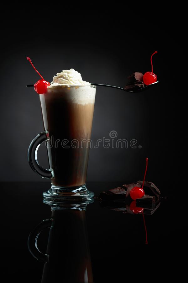 Layered coffee cocktail with whipped cream, cherry and pieces of chocolate. Black background stock photo