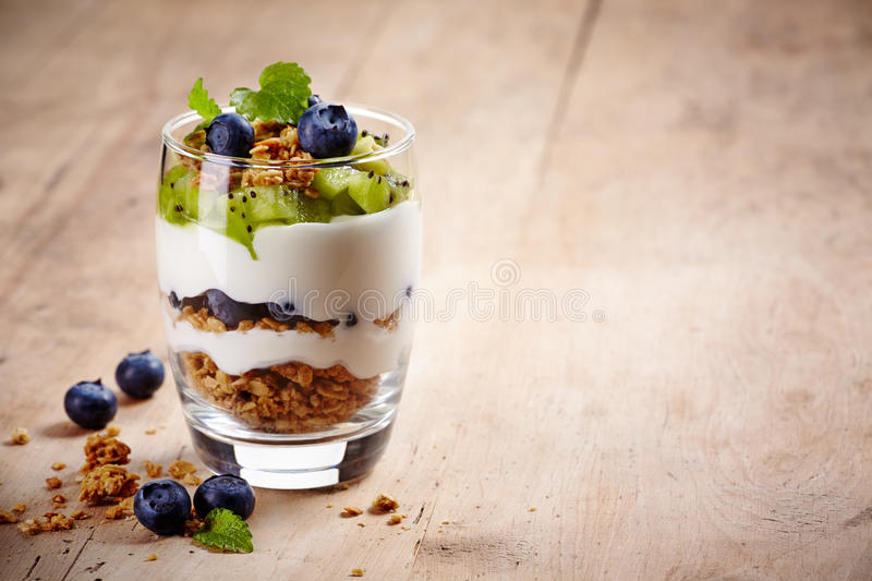 Layered cream dessert. Healthy layered dessert with cream, muesli, kiwi and blueberries on wooden background with space for text royalty free stock images