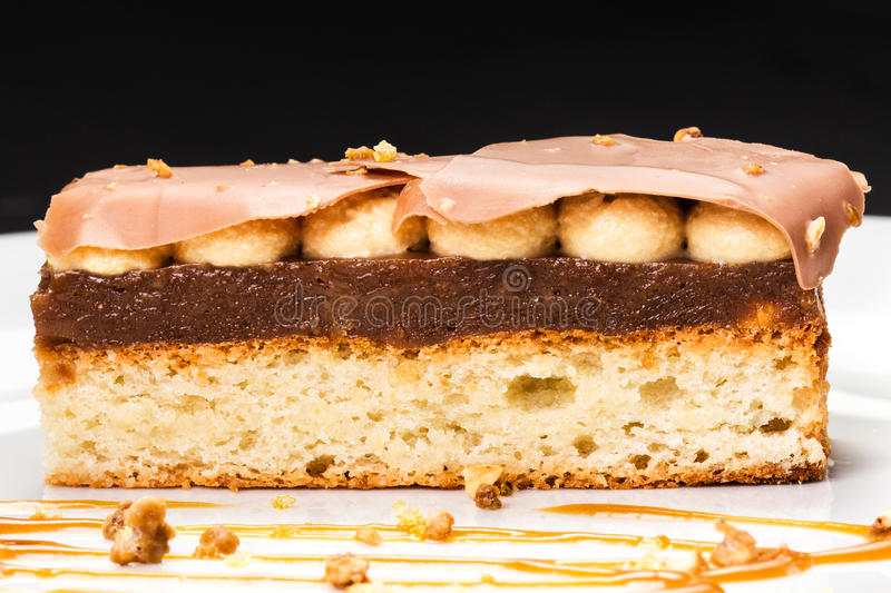 Layered dessert with caramel, nuts and chocolate on white plate, studio shot, macro stock images