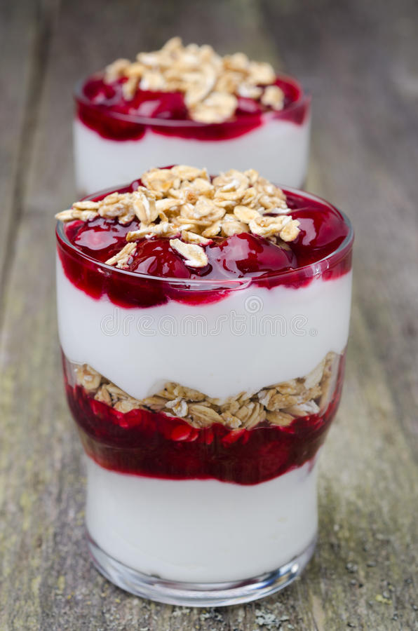 Layered dessert with yogurt and granola cherry. On the old wooden background, close-up stock photo