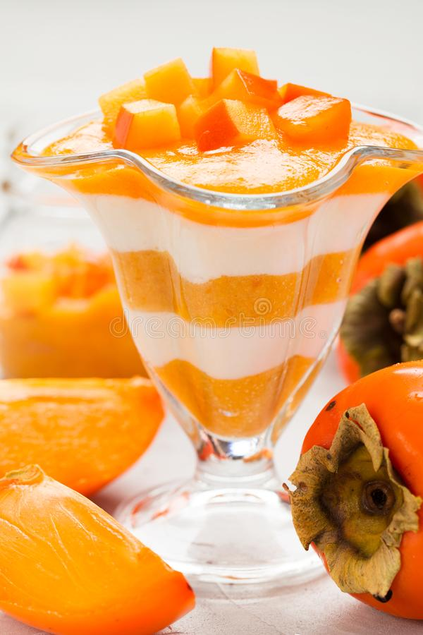 Layered dessert with yogurt and persimmon mousse with whole and cut ripe fresh fruit. On gray background - close up vertical photography of sweet healthy royalty free stock photo