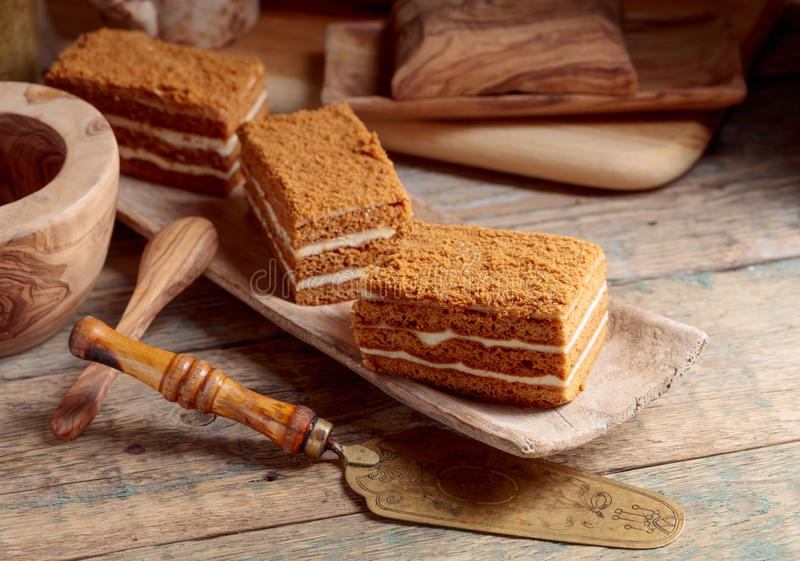 Layered honey cake with cream. Layered honey cake with white cream on a old wooden table stock photos