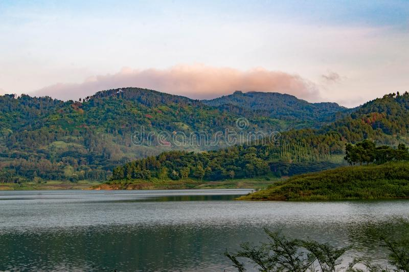 Layered mountains with beautiful lake views. Green and dark green on the water stock image