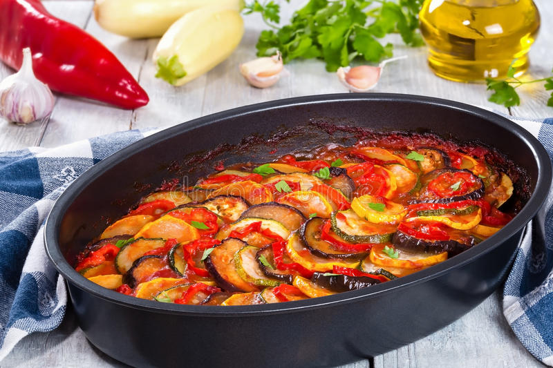 Layered ratatouille in a baking dish, close up. Layered ratatouille in a baking dish, slices of zucchini, red bell pepper, chili, yellow squash, eggplant, olive royalty free stock images
