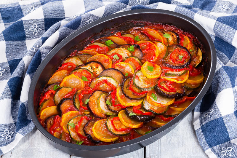 Layered ratatouille in a baking dish, close-up. Layered ratatouille in a baking dish, slices of zucchini, red bell pepper, chili, yellow squash, eggplant, olive stock photography