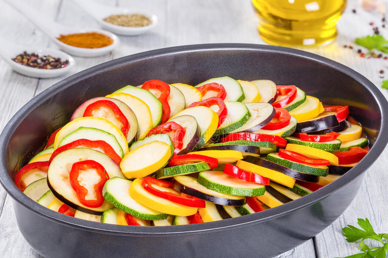 Layered ratatouille in a baking dish, close-up. Layered ratatouille in a baking dish, slices of zucchini, red bell pepper, yellow squash, eggplant, olive oil stock photography