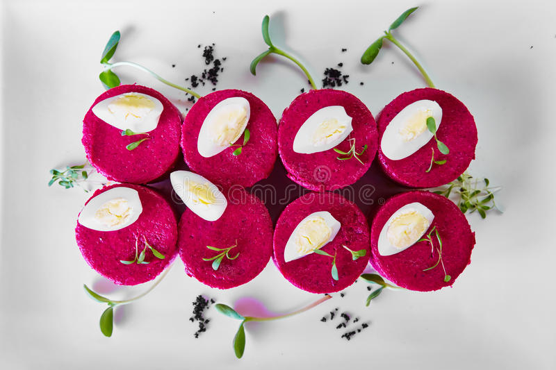 Layered salad with herring, beets, carrots, onions, potatoes and eggs close-up on a plate. horizontal. stock images