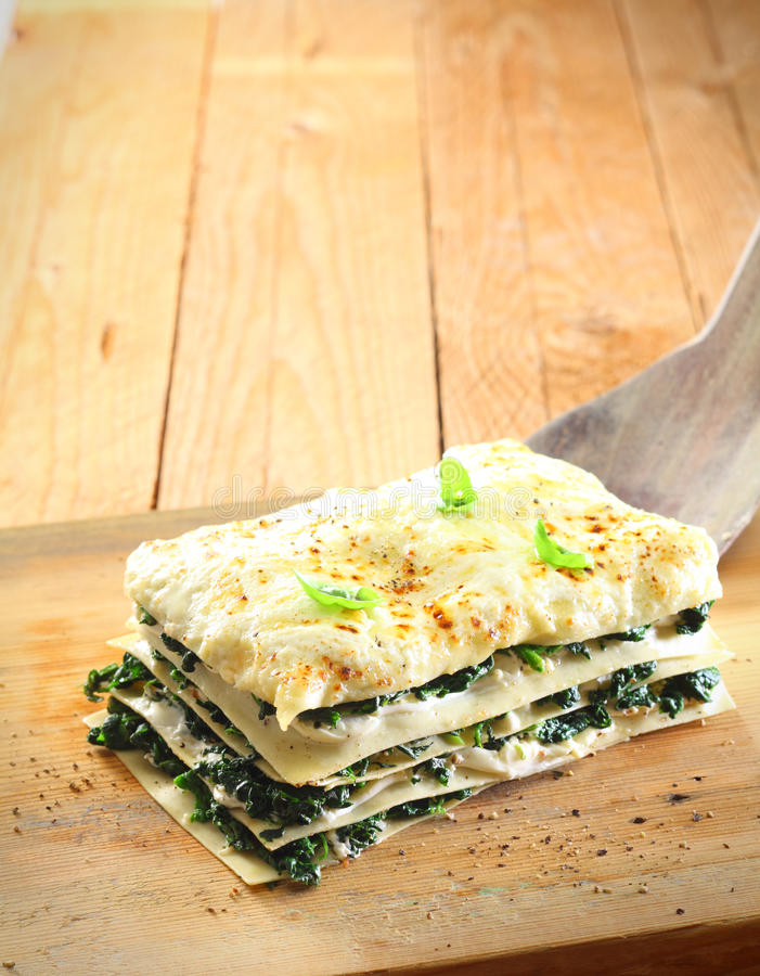 Layered spinach and cheese lasagne. On a wooden board for a nutritious vegetarian meal royalty free stock images