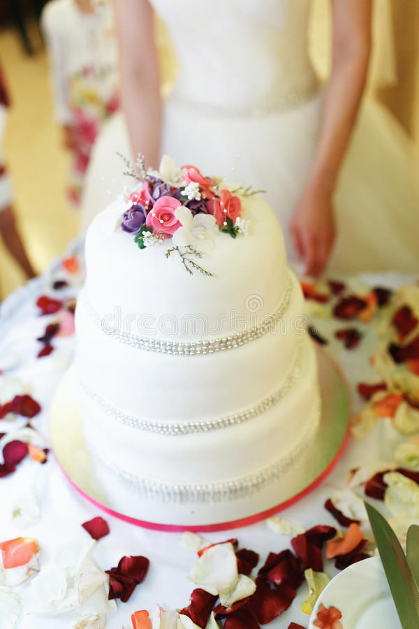 Layered wedding cake decorated with pearls and roses. A royalty free stock image