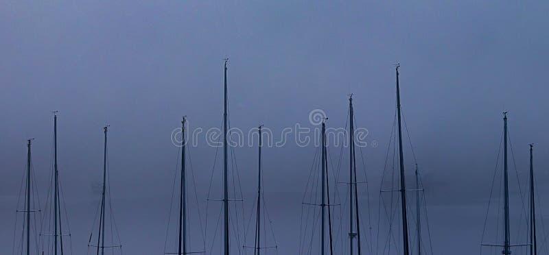 layers of fog behing sail boat masts royalty free stock photos