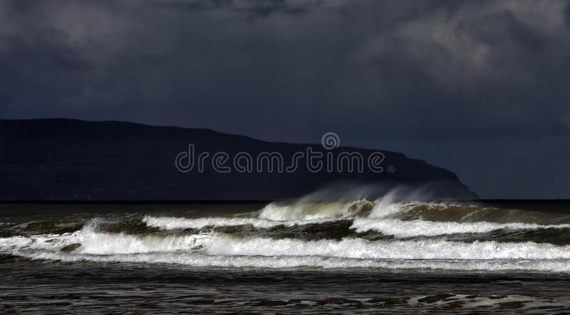 Layers of an incoming tide and storm on the Downhill Beach in the Downhill Demesne in County Londonderry in Northern Ireland. stock photo