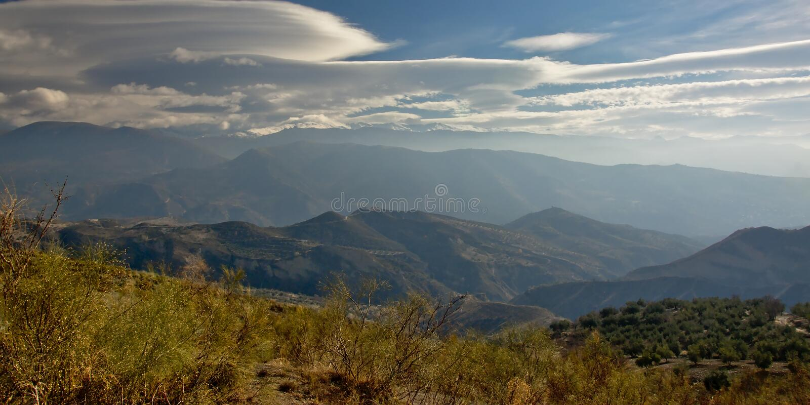 Sierra Nevada mountain landscape under a cloudy sky. Layers of Sierra Nevada mountains, lower ones with vegetation, the highest with snow under a cloudy sky stock photography
