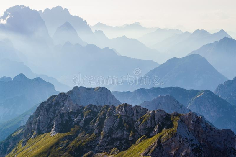 Layers of silhouettes of mountain ridges and peaks in the Italian Alps, at sunset. View from the route down from Mangart Mangrt royalty free stock image