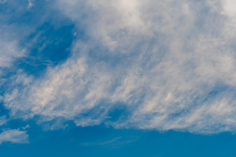 Layers of white cirrus clouds. In upper atmosphere in blue sky stock photography