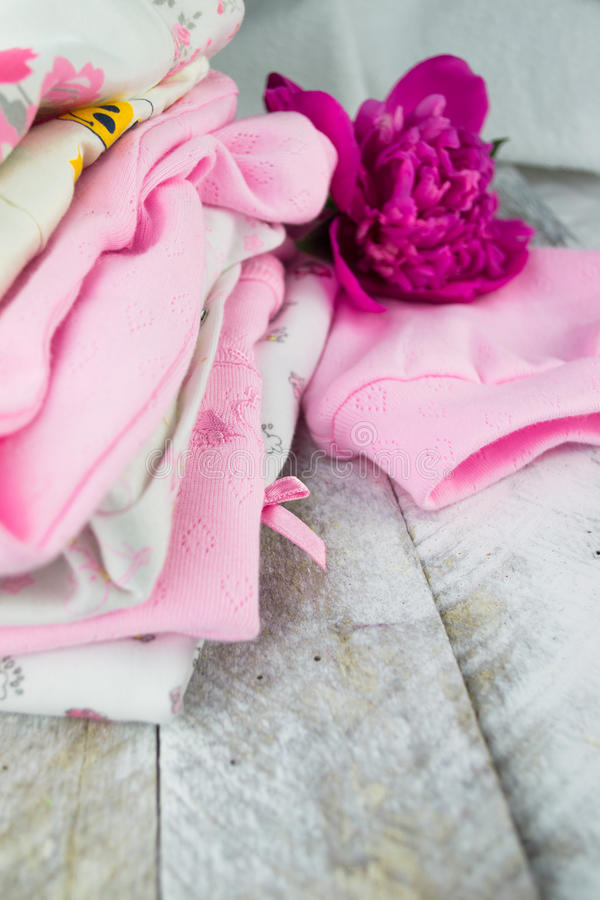 Layette rose pour un bébé nouveau-né avec le peone photo stock