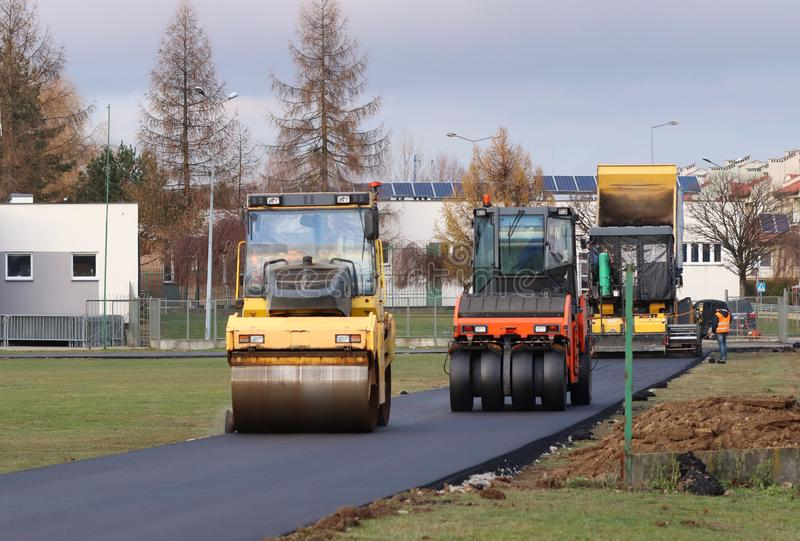 Laying asphalt with the help of heavy special equipment. The construction of the road. Modern technologies laying highway with a stock photo